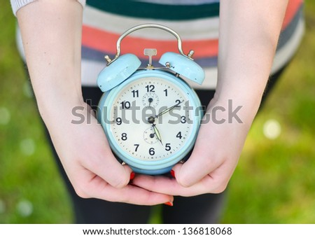 Hands holding old clock