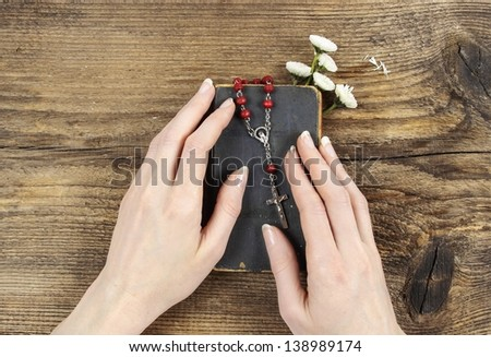 Hands holding old Holy Bible and red rosary. Wooden background. - stock photo