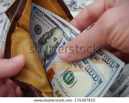 Hands Holding Open A Very Used And Worn Leather Wallet Holding Brand New United States One Hundred Dollar Federal Reserve Notes.  - stock photo