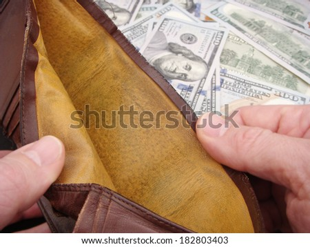 Hands Holding Open Empty Leather Wallet Over Brand New United States One Hundred Dollar Federal Reserve Notes.