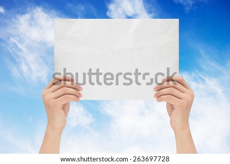hands holding or showing empty white crumpled paper with on blue sky background,business text concept. - stock photo