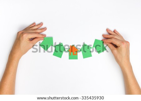 Hands holding paper house figure on white background. Real Estate green house Concept. Ecological building. Top view. - stock photo