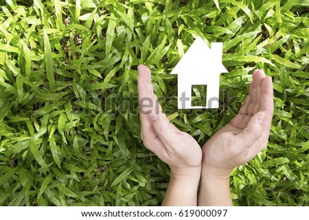 hands holding paper house over green grass.