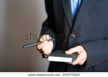 hands holding pen and notebook. advertising or business concept, isolated on a gray background.