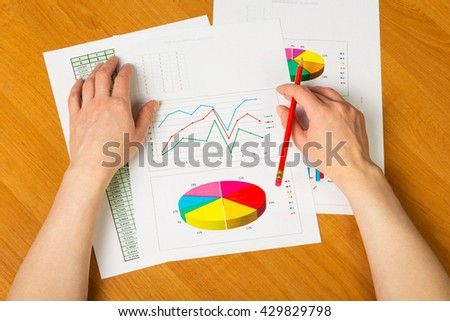Hands holding pen, calculations and graphics on the desktop background. - stock photo