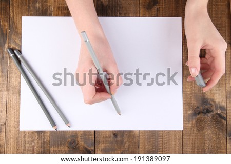 Hands holding pencil and erase with paper on wooden background