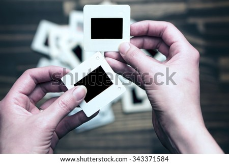 Hands holding photograph films with scattered photograph films on the background.