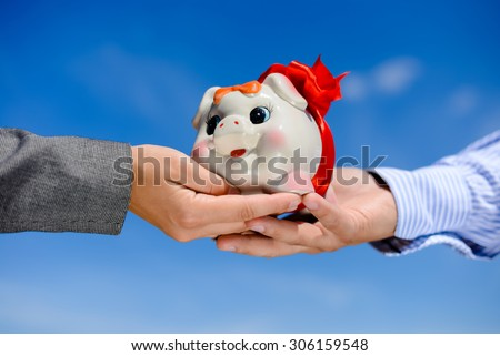 Hands holding piggy bank over blue sky sunny outdoors background copy space - stock photo
