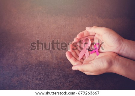 Hands holding Pink Ribbons toning background, Breast cancer awareness and Abdominal cancer awareness