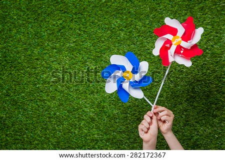 Hands holding pinwheels over grass