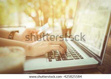 Hands holding plastic credit card and using laptop. hand using laptop in coffe shop - stock photo