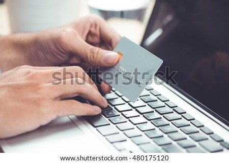 Hands holding plastic credit card and using laptop. Online shopping concept. Retro color.