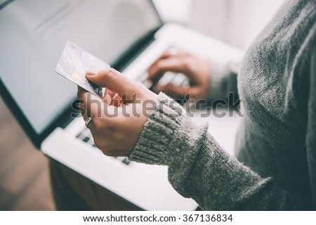Hands holding plastic credit card and using laptop. Online shopping concept. Toned picture - stock photo