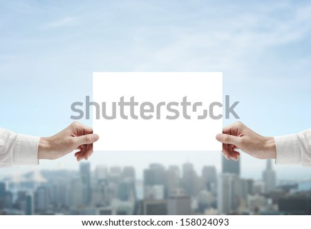 hands holding poster on city background