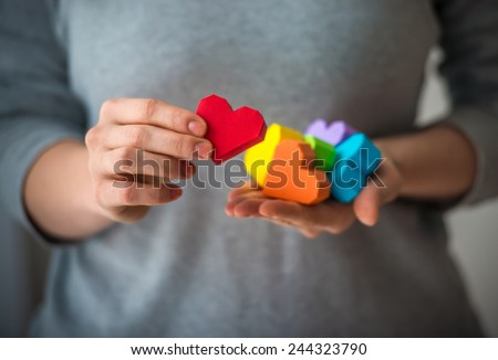 Hands holding  rainbow paper hearts, LGBT symbol. - stock photo