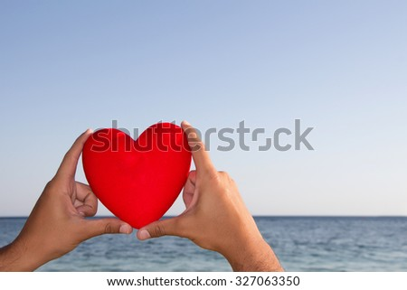 Hands holding red heart with blue sky and sea horizon in the background. - stock photo
