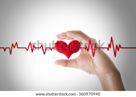 hands holding red heart with ecg line on white background, Heart or pulse rate concept. - stock photo