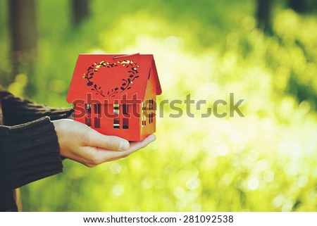 hands holding red model of house as symbol on natural garden background - stock photo