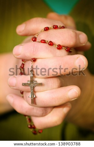 Hands holding red rosary with cross - stock photo