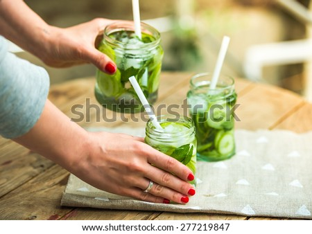 Hands holding retro glass jars of lemonade with cucumber and mint on wooden table