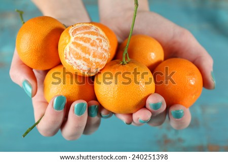 Hands holding ripe tangerines, close up - stock photo