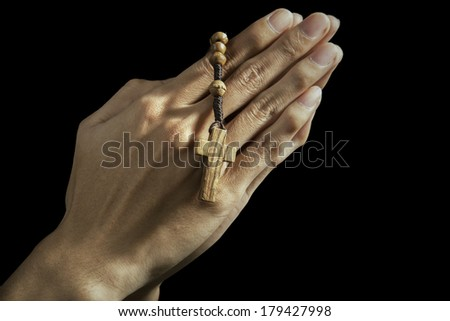 Hands holding rosary beads and cross while praying - stock photo