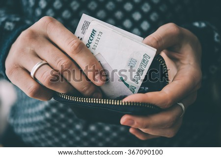 Hands holding russian rouble bills and small money pouch. Toned picture - stock photo