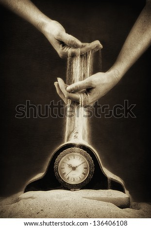 hands holding sand flowing down on a clock covered in sand - stock photo