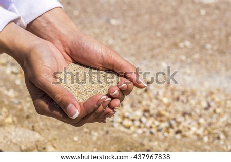 Hands holding sand from the beach