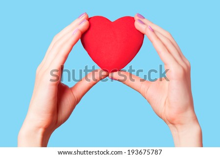 Hands holding shape heart on blue background.