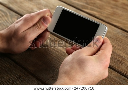 Hands holding smart mobile phone on wooden table background - stock photo
