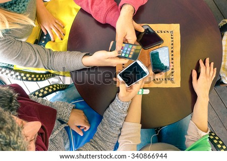 Hands holding smartphone top view - Mixed  group of friends having fun with mobile - Young students playing with telephone -  Concept of modern lifestyle and technology - Focus on mobile phones  - stock photo