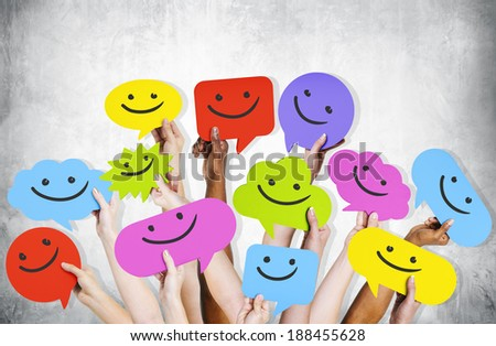 Hands holding smiley faces icons. - stock photo