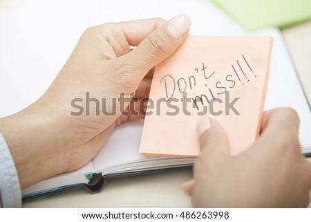 Hands holding sticky note with Do not miss text