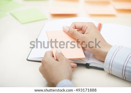Hands holding sticky note with empty space