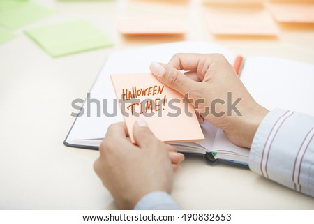 Hands holding sticky note with Halloween Time text