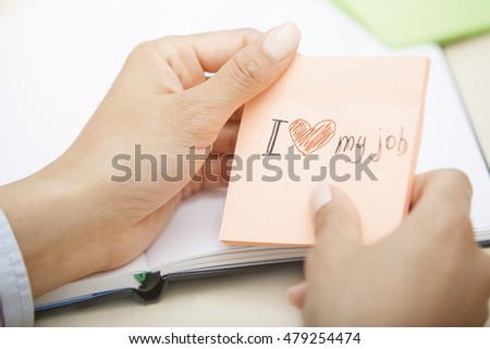 Hands holding sticky note with Love my job text