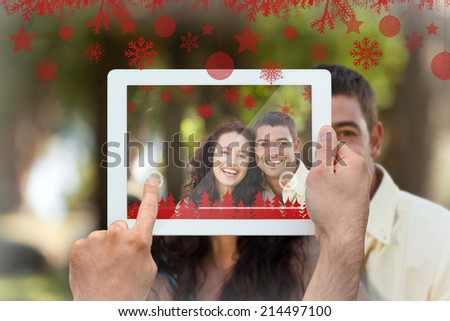 Hands holding tablet pc against couple sitting in the garden - stock photo