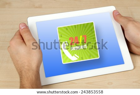 Hands holding tablet PC on wooden table background, Round-the-clock service concept - stock photo