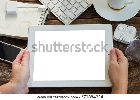 Hands holding tablet with copy space on scree over wooden working table with frame of gadgets - stock photo
