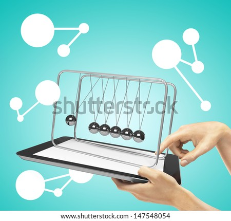 hands holding tablet with newton's cradle - stock photo