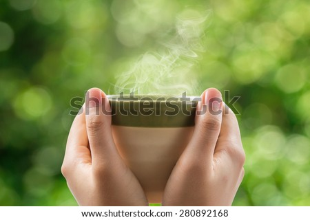 Hands holding tea cup on green bokeh background. - stock photo