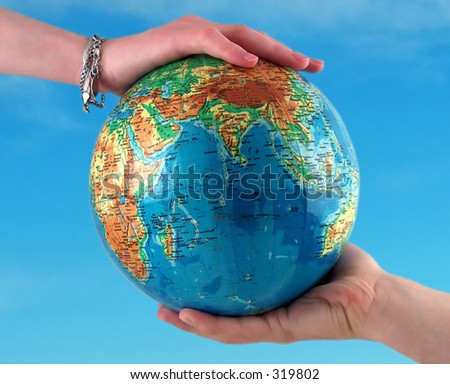 hands holding the earth, clear sky background - stock photo