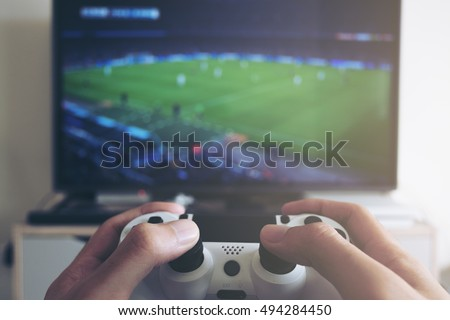 Hands holding the game controller while man playing game on TV in a room