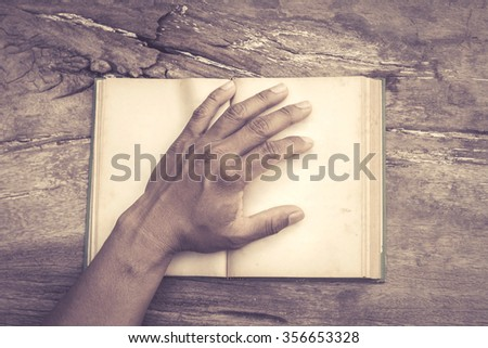 hands holding the old book on old wooden table - stock photo