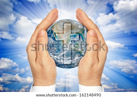 "Hands holding the planet Earth with the Christian cross .""Elements of this image furnished by NASA"" - stock photo"