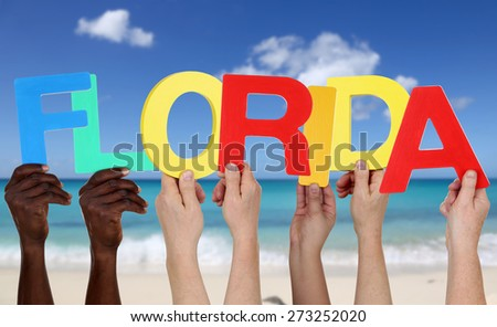 Hands holding the word Florida in summer on sea and beach - stock photo