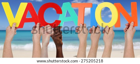 Hands holding the word vacation on beach, sand and sea - stock photo
