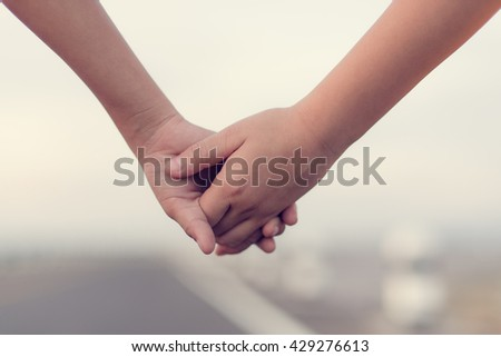 Hands holding together, boy and girl holding hands.  Depth of field