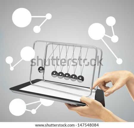 hands holding  touch pad with newton's cradle - stock photo